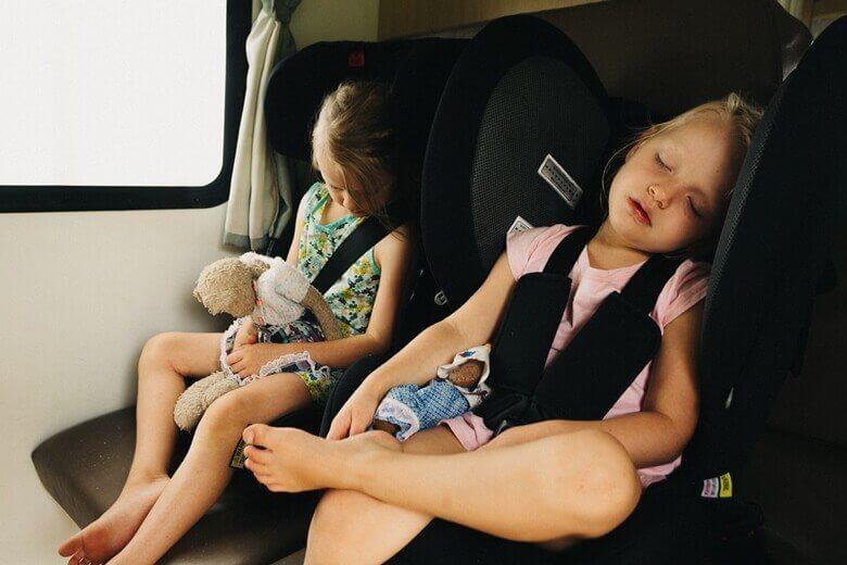Kindersitze im Wohnmobil mit zwei schlafenden Mädchen