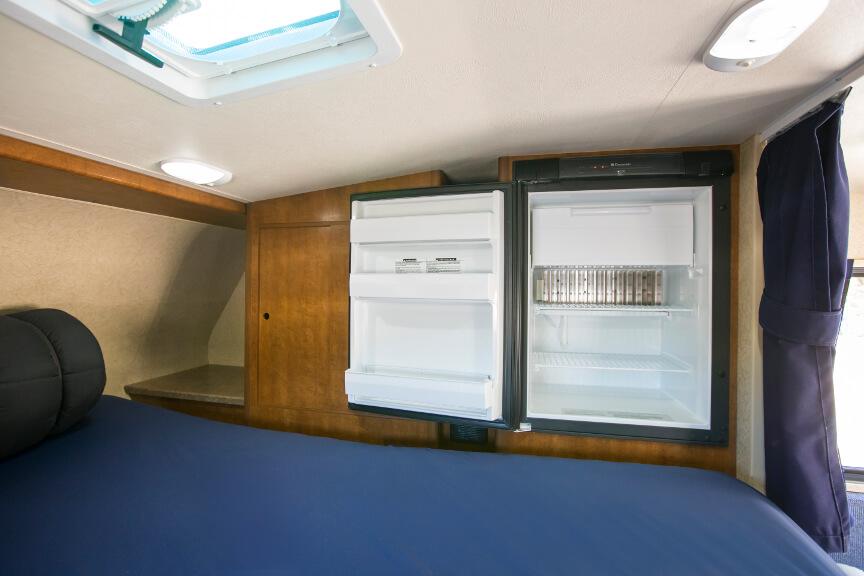 Offener Kühlschrank neben dem Alkoven-Doppelbett