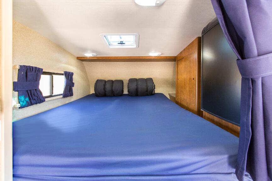 Alkoven-Nische mit Doppelbett, Fenster und Kühlschrank