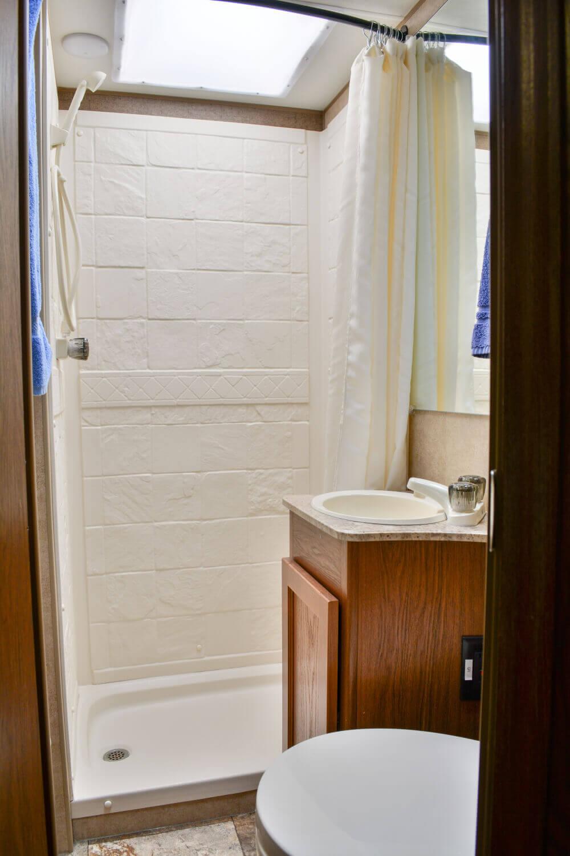 Badezimmer mit Dusche, Waschbecken und WC