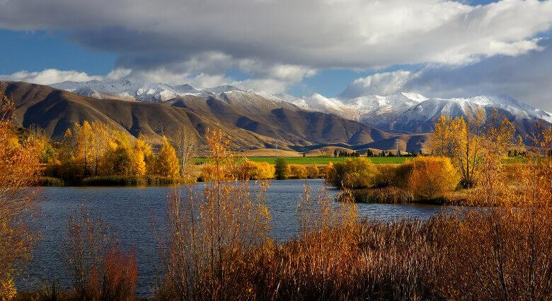 See, Berge und Bäume in strahlenden Herbstfarben