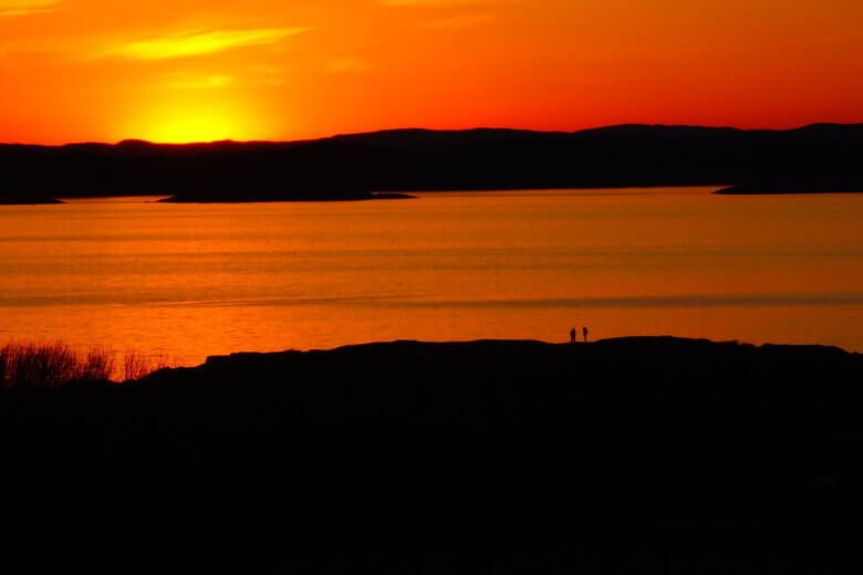 Romantischer Sonnenuntergang mit Wanderern in der Ferne