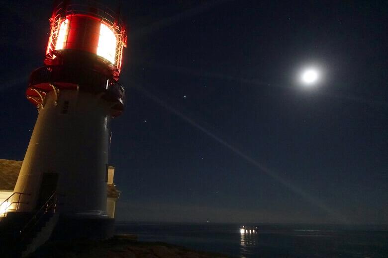 Lindesnes Leuchtturm und vorbeifahrendes Schiff bei Nacht