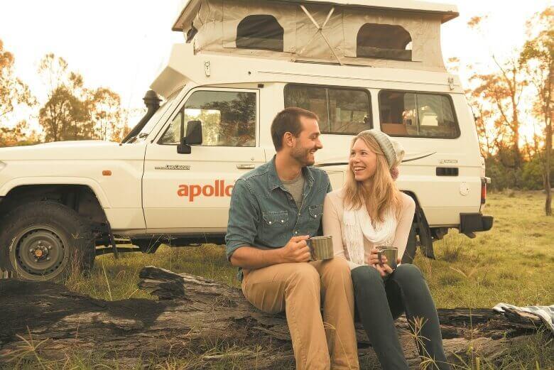Pärchen sitzt vor einem Allrad Camper von Apollo