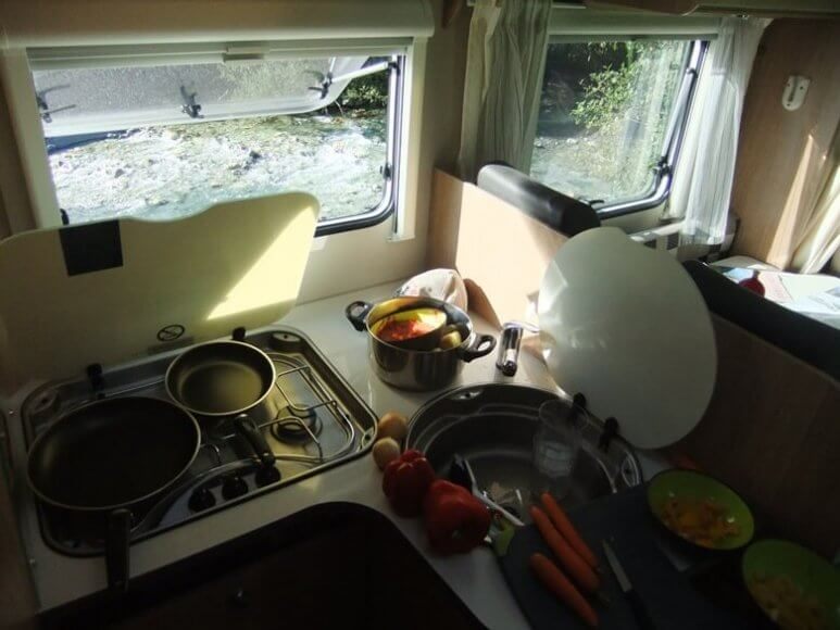Kochen im Wohnmobil mit Blick auf Fluss in der Schweiz
