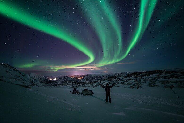 Schneemobil unter den Polarlichtern im Norden von Norwegen