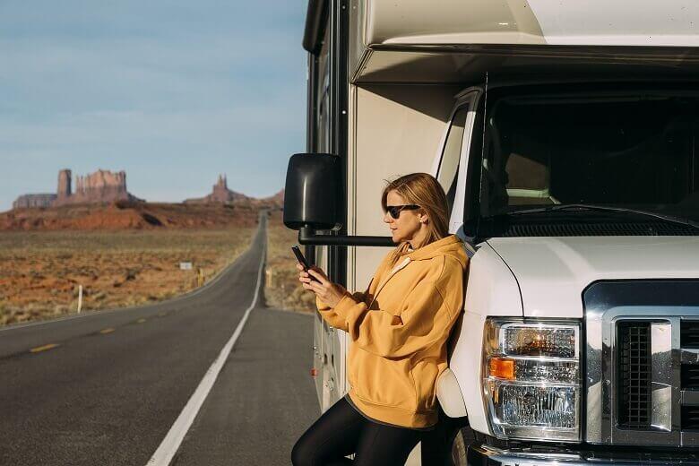 Frau steht am Wohnmobil und schaut auf ihr Smartphone