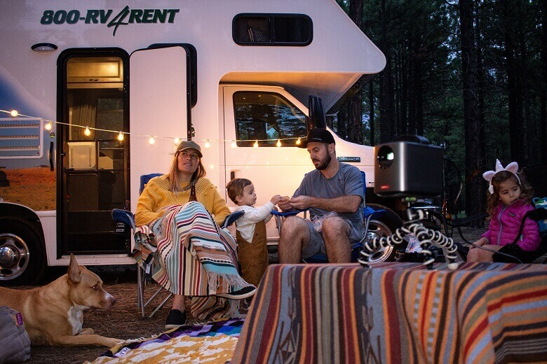Familie sitzt am Abend auf dem Campingplatz vor dem Wohnmobil