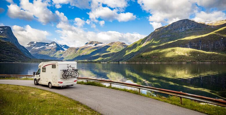 Nachhaltig reisen: Wohnmobil mit Fahrrädern fährt durch die Natur.