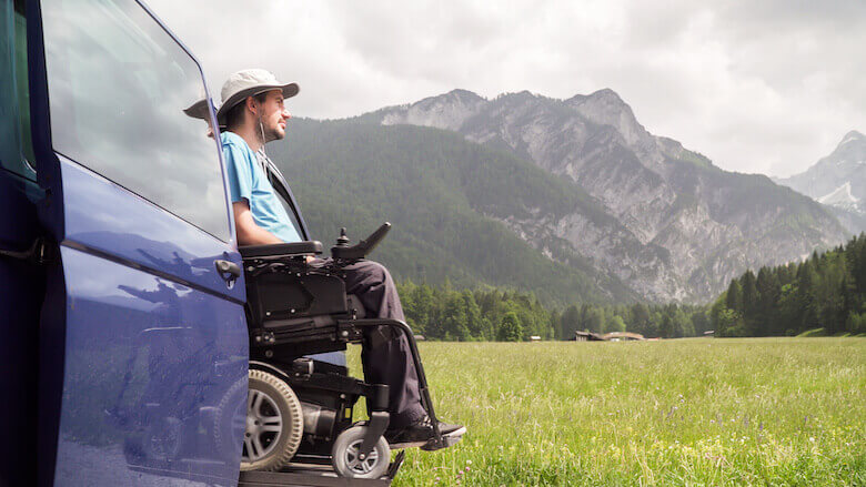 Campingfahrzeug mit Rollstuhllift parkt auf einer Wiese mit einer Berglandschaft im Hintergrund.