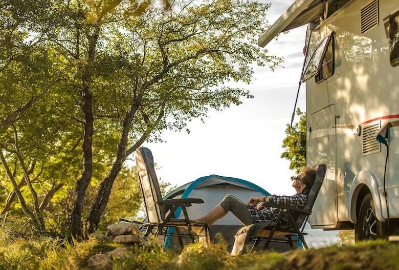 Camping für Senioren: Ältere Dame entspannt sich auf Campingstühlen vor ihrem Wohnmobil.