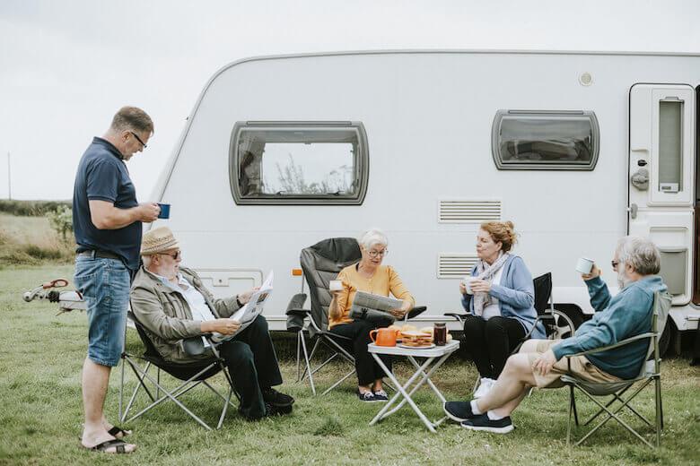 Camping für Senioren: Camper-Pärchen entspannen gemeinsam vor dem Wohnwagen.