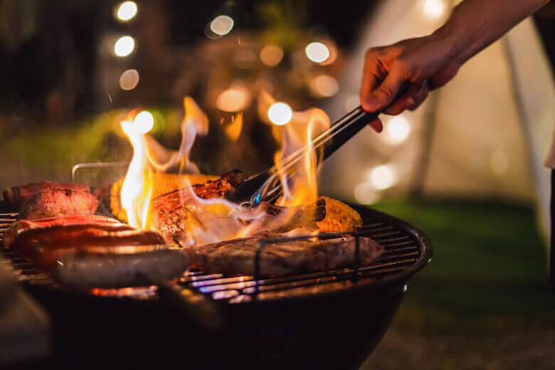 Im Urlaub sparen – Mann grillt auf dem Campingplatz.