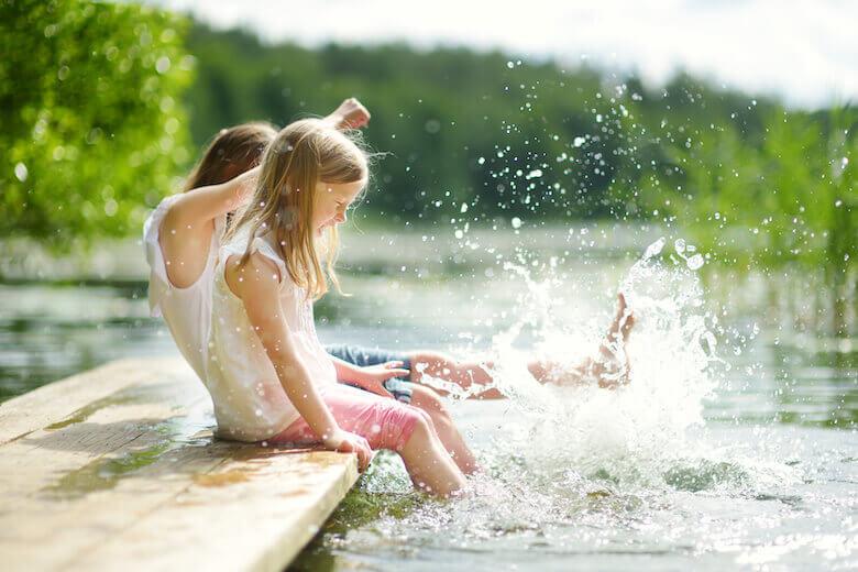 Campingplatz für Kinder: Geschwister planschen gemeinsam in einem Badesee.