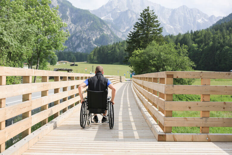 Rollstuhlfahrer nutzt barrierefreie Wege auf einem Ausflug in der Natur.
