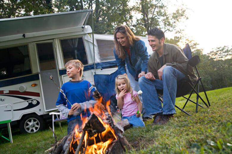 Camping mit Kindern: Familie grillt gemeinsam vor dem Wohnmobil.