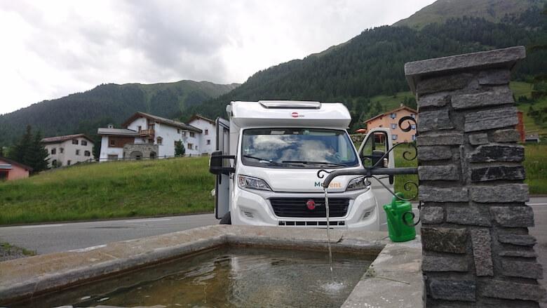 Wohnmobil an einem Dorfbrunnen