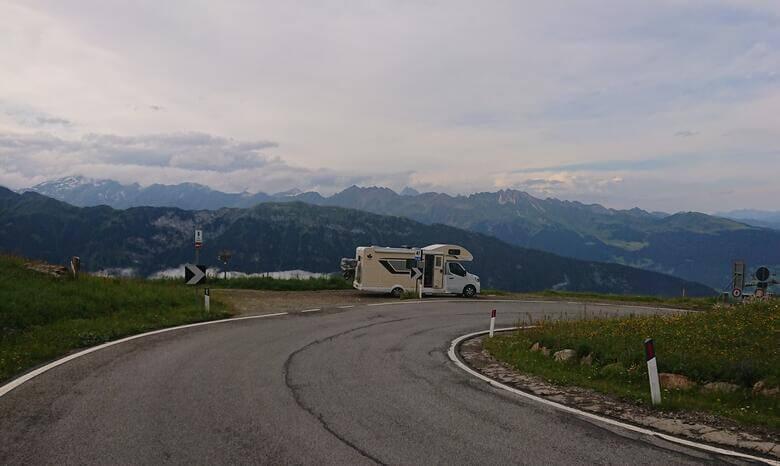 Camper am Straßenrand mit Alpenpanorama im Hintergrund