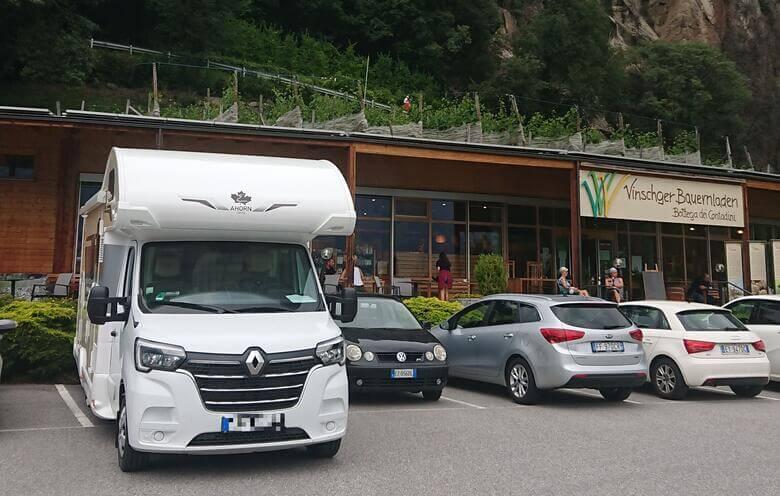 Wohnmobil steht vor einem Hofladen im Vinschgau.