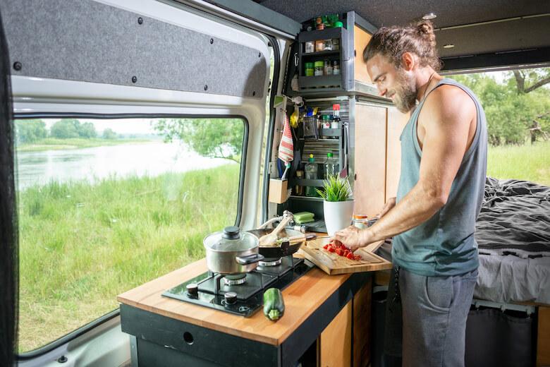 Nachhaltig campen: Mann schneidet frisches Gemüse in der Wohnmobilküche