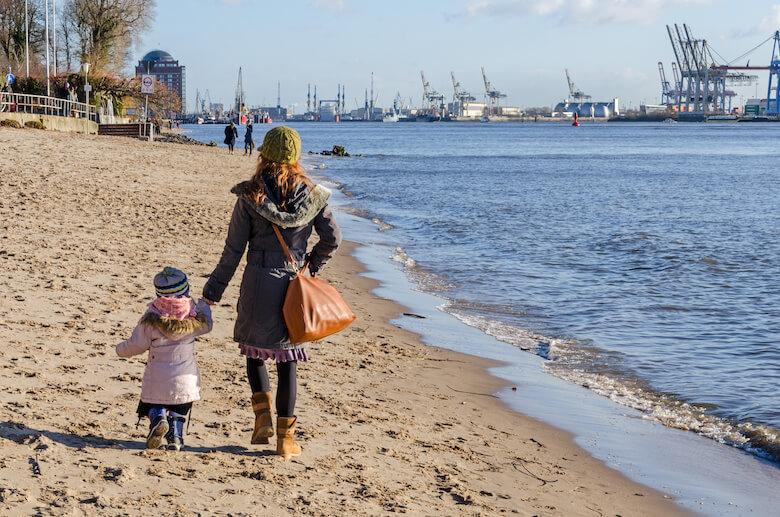 Mutter und Kinder spazieren am Elbufer.