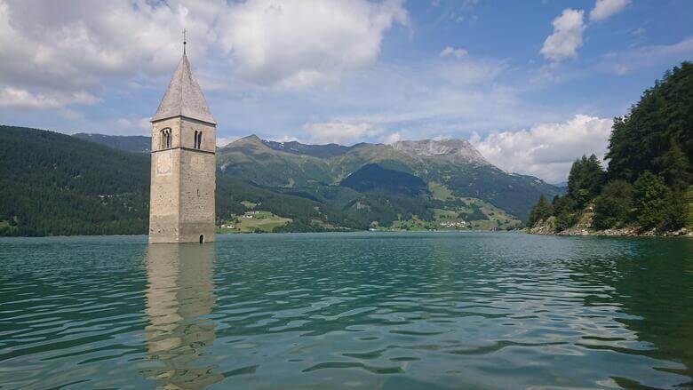 Ein Kirchturm ragt aus dem Reschensee in Graun im Vinschgau