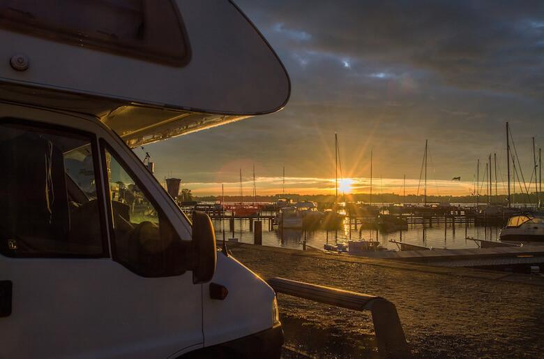 Wohnmobil steht im Hafen bei Sonnenuntergang.